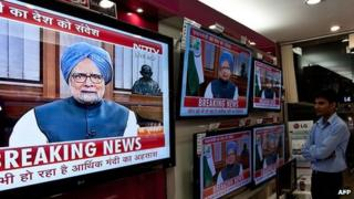 Salesmen in New Delhi, India watch Prime Minister Manmohan Singh address the country, 21 September 2012