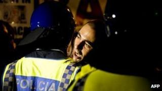 A protester is held back by police outside the presidential palace