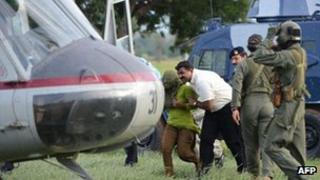 Pakistani security personnel shift Rimsha Masih (L), a Christian girl accused of blasphemy, to a helicopter after her release from jail in Rawalpindi