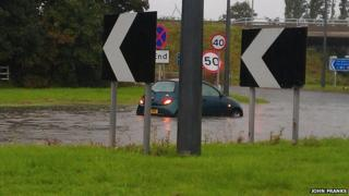 Car partly submerged in floodwater on road