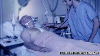 Member of medical staff using a stethoscope to listen to the chest of a male patient in an intensive care unit