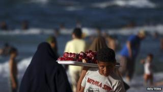 Boy selling toffee apples on the beach at Alexandria, Egypt (file photo - 7 Sept 2012)