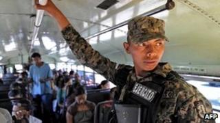 Honduran soldier riding a public bus in Tegucigalpa