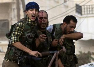 An injured rebel fighter is helped to safety in Aleppo, Syria, 27 September