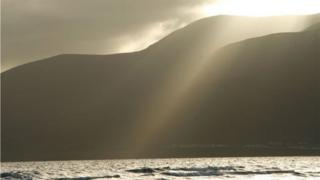 Shaft of sunlight on mountain and sea