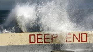Wave crashing over deep end sign