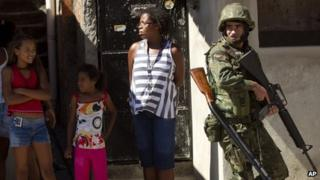 Residents watch soldiers patrolling the Fogo Cruzado slum in Rio de Janeiro ahead of Sunday's municipal elections