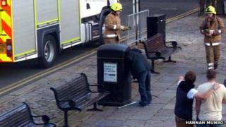Man with head stuck in bin