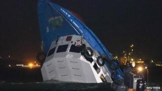 Rescuers approach a partially-submerged boat after two vessels collided off Hong Kong on 1 October 2012