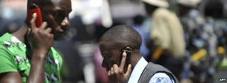People walk while speaking on the phone on 1 October 2012 in Nairobi, Kenya