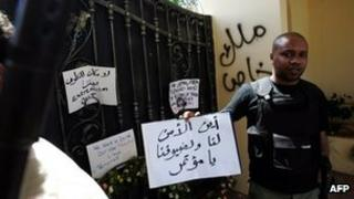 """A Libyan security guard holds a slogan, which reads in Arabic """"Where is the security for us and for our guests"""" at the main entrance of the US consulate in Benghazi on 18 September 2012"""