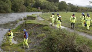 A coastguard search team searching along the River Dyfi in Machynlleth