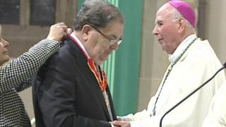John Hume receives the honour from Bishop Edward Daly