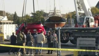 The red car is lifted out of the water