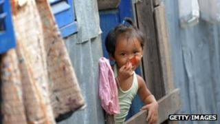 Cambodian girl looking out of a window