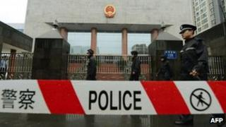 Police officers stand guard outside the Chengdu People's Intermediate court in Chengdu, China, 24 Sept 2012