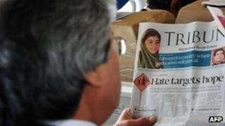 A Pakistani passenger reads a local newspaper featuring news of Malala Yousafzai
