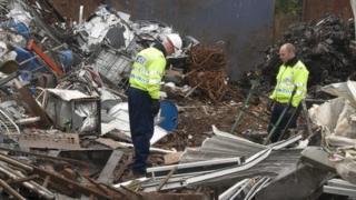 Two police officers in a scrap metal yard
