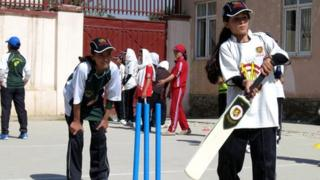 Schoolgirls playing cricket