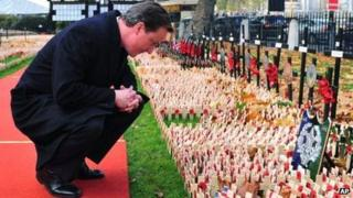 David Cameron pictured in 2009 looking at commemorative crosses