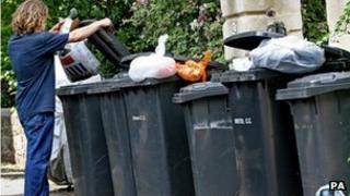 Man emptying rubbish into wheelie bin