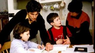 A family does homework in kitchen
