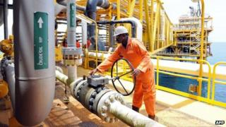 A file photo taken on April 14, 2009 shows a worker inspecting facilities on an upstream oil drilling platform at the Total oil platform at Amenem, 35 kilometres away from Port Harcourt, Nigeria.