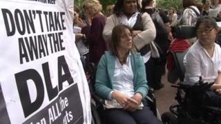 Protesters beside placard defending the disability living allowance