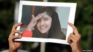 Someone holding a picture of Malala Yousafzai.