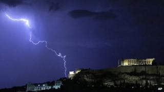 Lightning illuminates the ancient Parthenon temple on top of the Acropolis hill in Athens on 14 October 2012