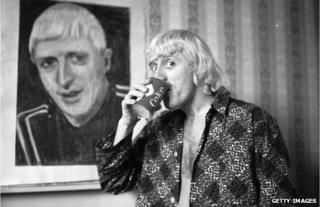 Jimmy Savile poses by a portrait of himself, painted by a friend, in 1965