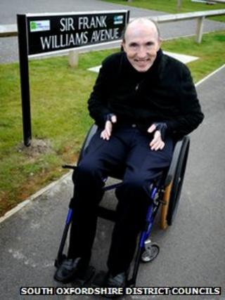 """Sir Frank next to the """"Sir Frank Williams Avenue"""" sign"""