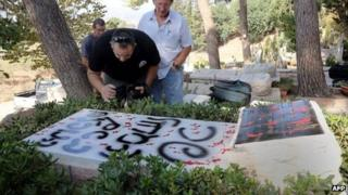 Men inspect the damage done to Moshe Dayan's grave (16 October 2012)