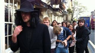 A child catcher leading the children down the street
