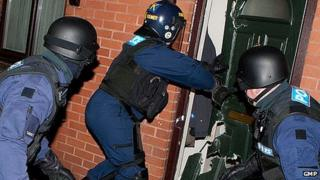 Police officers raid a house in Manchester