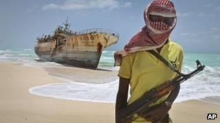 Somali pirate Hassan stands near a Taiwanese fishing vessel that washed up on shore after the pirates were paid a ransom and released the crew, Hoboyo, Somalia 23 September 2012