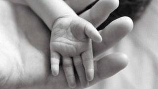 Baby's hand resting on adult palm
