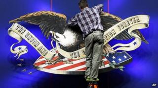 A worker prepares the backdrop for Monday's presidential campaign debate in Boca Raton, Florida, 21 October 2012