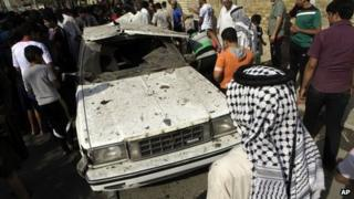 People inspect a car damaged by car bombings in Shula, Baghdad (23 October 2012)