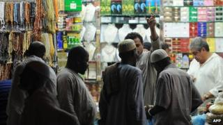 African Muslim pilgrims shop close to the Grand Mosque in the holy city of Mecca, on October 23, 2012.