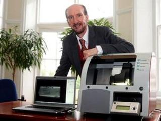 Dr John Bond stands with CERA machine