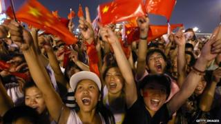 Chinese crowd in Beijing waving flags