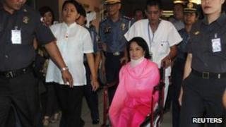 Former Philippine President Gloria Macapagal Arroyo, now a sitting lawmaker in the lower house of Congress, sits on a wheelchair on her way towards the Sandiganbayan anti-graft court in Quezon City, Metro Manila 29 October, 2012