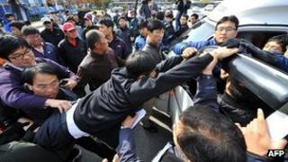 South Korean activists inside a truck scuffle with local residents as plainclothes police officers try to separate them following the launch of anti-North Korea leaflets across the border at a park in the border town of Paju on 29 October, 2012