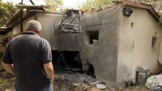 Israel man looks at building in Kibbutz Beeri damaged by rocket-fire from Gaza (24/10/12)