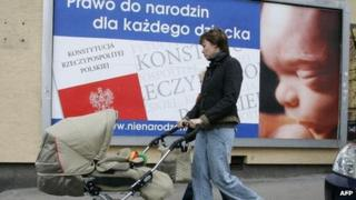 """A mother with a child passes a poster with inscription """"Right to be born for every child"""" in Warsaw 15 March 2007"""