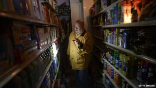 A man shops for groceries using a flashlight