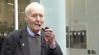 Tony Benn smoking his pipe outside the building named in his honour