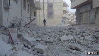 A rebel fighter walks near a building damaged after an air strike on Maarat al-Numan, 31 October 2012
