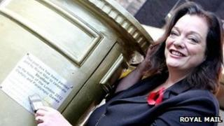 Lyn Brown MP and golden postbox plaque in Stratford